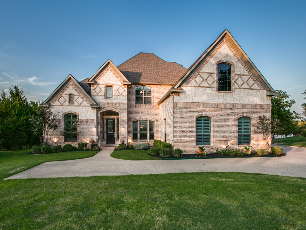 Beautifully manicured landscaping create sought-after curb appeal. The gorgeous up-lighting looks majestic at night.