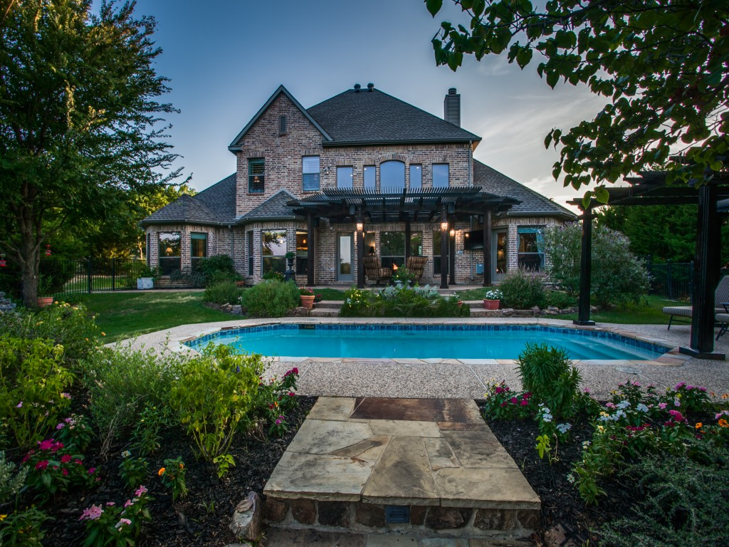 Manicured gardens under mature Oak trees leads you through the large, grassy backyard and the lake beyond. You could build a fire-pit here and watch the sun set with your friends..
