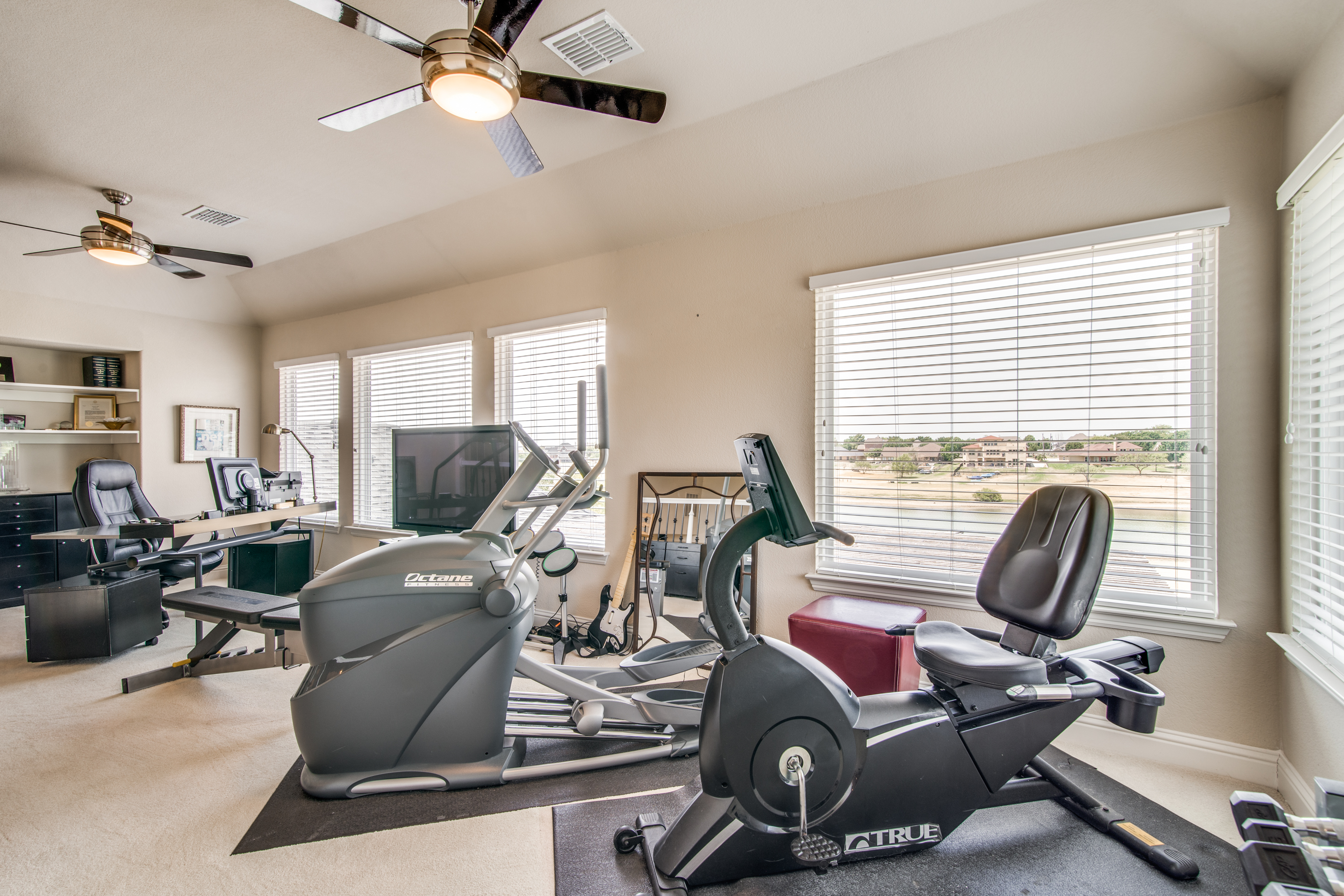 The upstairs loft with a wall of windows with a gorgeous lake view. The current owner uses this as a fitness room, however as a bonus space would do well as whatever you choose.