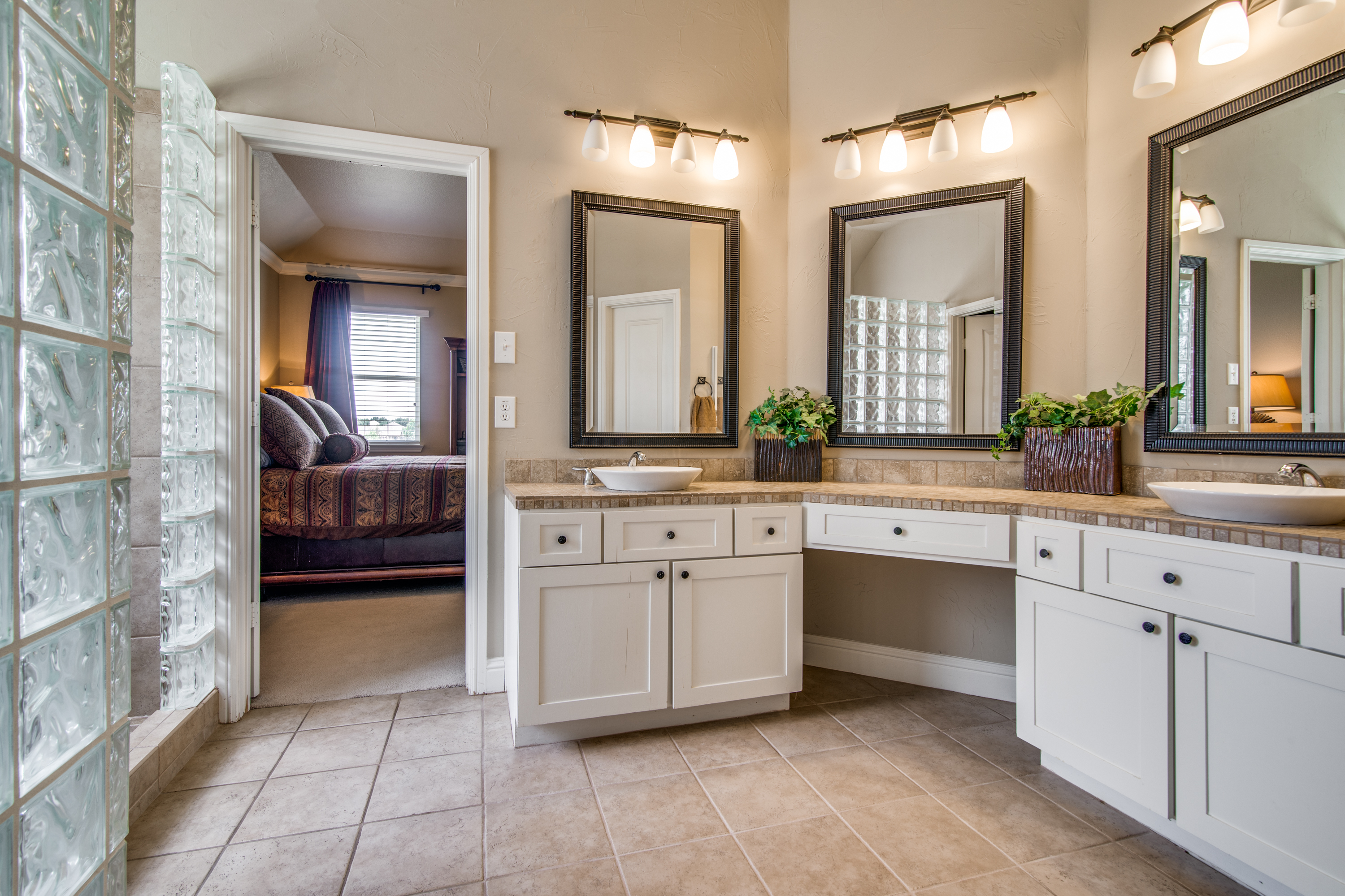 Dual sink vanities with a sitting area, walk in closet & separate standing shower.